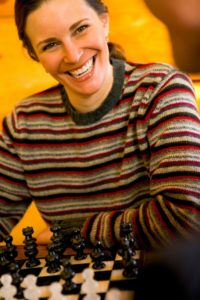 smiling young lady plays chess