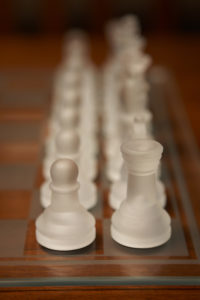 photo of white glass chess pieces